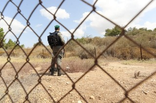 Israeli soldier stands on guard at a checkpoint in the northern West Bank