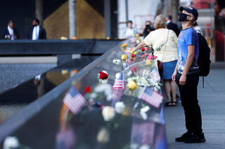 People place flags and flowers at the South Tower, before ceremonies marking the 20th anniversary of the September 11 attack, in New York