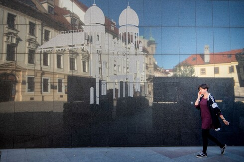 A woman passes a wall with an image of the former Neolog Synagogue next to the Holocaust Memorial located in the center of Bratislava's Old Town