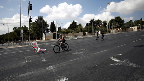 Israelis on bikes in an empty street during the Jewish Holiday of Yom Kippur in Jerusalem, 16 September 2021