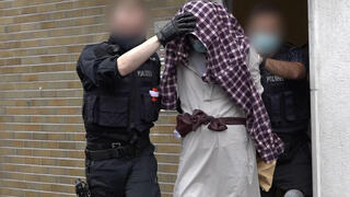 A man is taken away by police officers in connection with the suspected planned attack on the Hagen synagogue