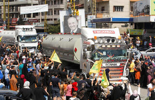 People wave Hezbollah flags as a convoy of tanker trucks carrying Iranian fuel arrives in Baalbek, Lebanon, on Thursday