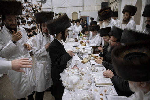 Tabersky, left, presents his firstborn son Yossef on a silver platter to Jewish priests from the Lelov Hassidic dynasty, during a pidyon haben ceremony in Beit Shemesh, Israel, Thursday, Sept. 16, 2021