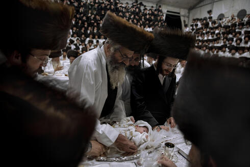 Yaakov Tabersky, right, presents his firstborn son Yossef on a silver platter to Jewish priests from the Lelov Hassidic dynasty, during pidyon haben ceremony in Beit Shemesh, Israel, Thursday, Sept. 16, 2021