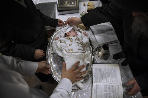 Yaakov Tabersky, left, presents his firstborn son Yossef on a silver platter to Jewish priests from the Lelov Hassidic dynasty, during a pidyon haben ceremony in Beit Shemesh, Israel, Thursday, Sept. 16, 2021