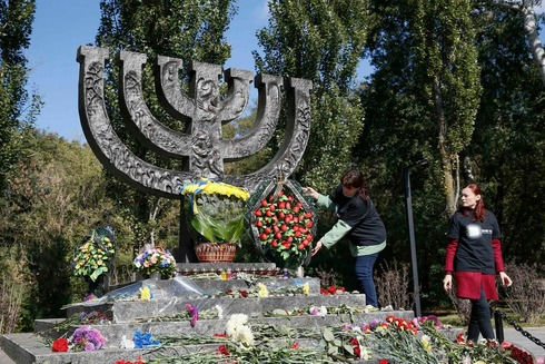 A woman places flowers at a monument commemorating the victims of Baby Yar (Babiy Yar), one of the biggest single massacres of Jews during the Nazi Holocaust