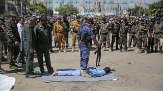 An executioner stands over a man convicted of being involved in the killing of senior Houthi official Saleh al-Samad, Saturday, Sept. 18, 2021, in Tahrir Square in Sanaa, Yemen