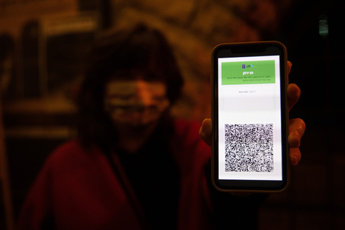 A woman shows the Green Pass on her phone