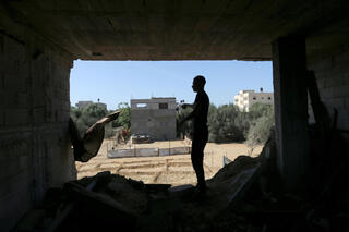 A Palestinian man stands inside a house that was damaged by Israeli strikes during Israel-Hamas fighting last May, in Khan Younis in southern Gaza Strip