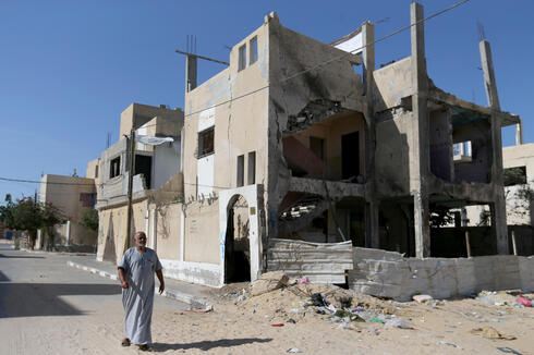 A Palestinian man walks outside a house that was damaged by Israeli strikes during Israel-Hamas fighting last May, in Khan Younis in southern Gaza Strip
