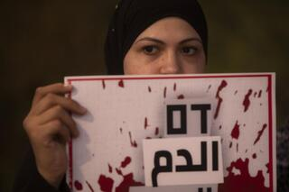Protesters hold signs and chant slogans during a demonstration against violence near the house of Public Security Minister Omer Barlev in the central Israeli town of Kokhav Ya'ir; sign reads: 'Blood'