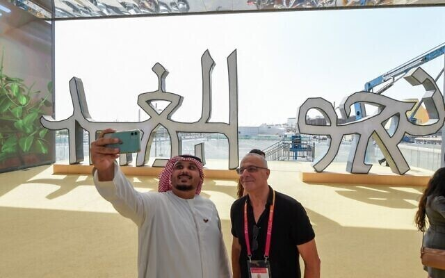 A visitor takes a selfie with Israeli pavilion official Josh Bendit in front of a sign reading 'toward tomorrow' in words written in characters that can be read by both Hebrew and Arabic speakers during a media preview