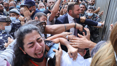 Activists and relatives of victims of the Beirut port explosion scuffle among themselves as Lebanese security members try to interfere during a demonstration on September 29, 2021 outside the capital's Justice Palace