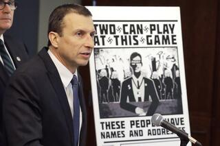 Raymond Duda, special agent in charge in Seattle, speaks as he stands next to a poster that was mailed earlier in the year to the home of Chris Ingalls, an investigative reporter with KING-TV in Seattle, during a news conference