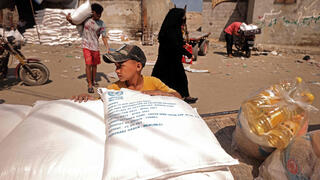 Palestinians collect food aid at a distribution centre run by United Nations Relief and Works Agency (UNRWA), in Gaza City
