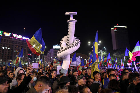 Protesters holding a makeshift syringe with a knot attend a rally against new restrictions in Romania on Saturday