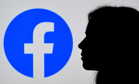 photo illustration, a person looks at a smart phone with a Facebook App logo displayed on the background