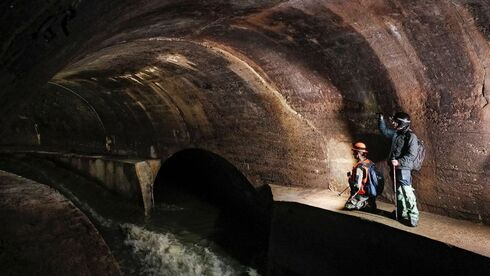 Diggers Andriy Ryshtun and Oleksandr Ivanov explore the city sewage system where dozens of Jews were hiding from the Nazis during World War Two in Lviv, Ukraine September 25, 2021.