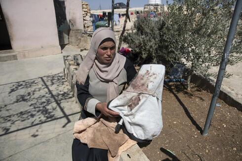 Palestinian mother Baraa Hamamdi holds her injured son's bloodstained clothes that was left behind after Mohammed was evacuated to an Israeli hospital, following a settlers attack from nearby settlement outposts