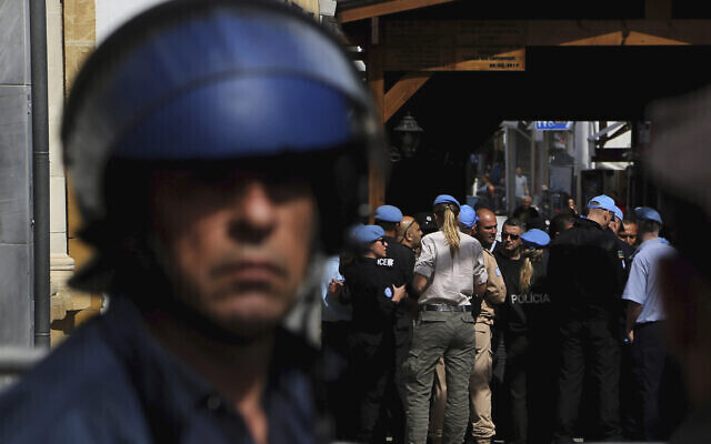 A Greek police officer, foreground, stands guard as UN peacekeepers block the closed crossing point in the divided capital of Nicosia, Cyprus