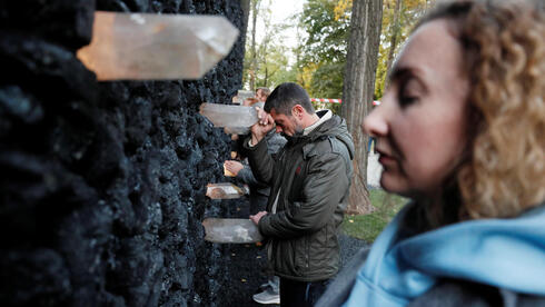 """People take part in a performance by artist Marina Abramovic next to her artwork """"Crystal Wall of Crying"""" at Babyn Yar, the site of one of the biggest massacres of the Holocaust during World War Two, in Kyiv, Ukraine"""