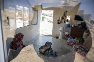 A Palestinian family is seen through their house's shattered window following a settlers' attack from nearby settlement outposts on the West Bank village of al-Mufagara,