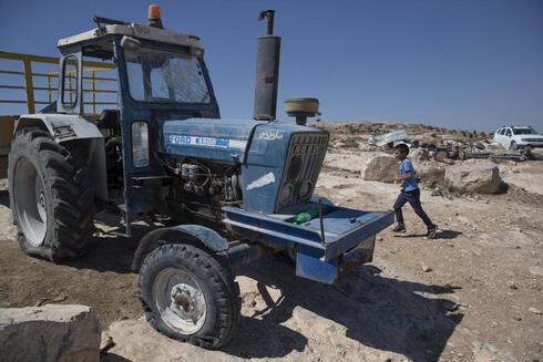 A tractor with a shattered windshield and flat tires following a settlers' attack from nearby settlement outposts on the Palestinian Bedouin community, in the West Bank village of al-Mufagara,