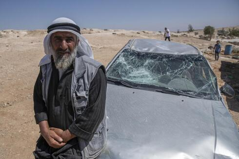 A Palestinian man leans on his smashed vehicle following a settlers attack from nearby settlement outposts on his Bedouin community, in the West Bank village of al-Mufagara