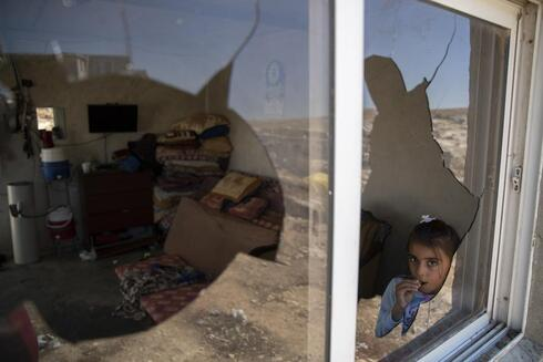 A Palestinian girl is seen through her family house's shattered window following a settlers' attack from nearby settlement outposts on the Bedouin community, in the West Bank village of al-Mufagara