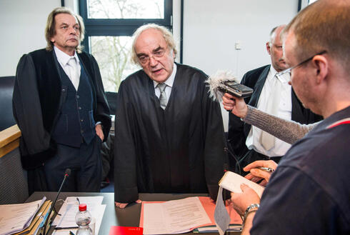 Prosecutor Thomas Walther, center, speaks to reporters on the first day of the trial against former SS medic Hubert Zafke, accused of aiding in 3,681 murders in Auschwitz in 1944, at the regional court of Neubrandenburg, February 29, 2016