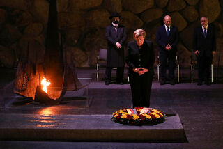 Outgoing German Chancellor Angela Merkel pauses after laying a wreath at the Hall of Remembrance, as Prime Minister Naftali Bennett, second right, looks on during a visit to the Yad Vashem Holocaust Museum in Jerusalem