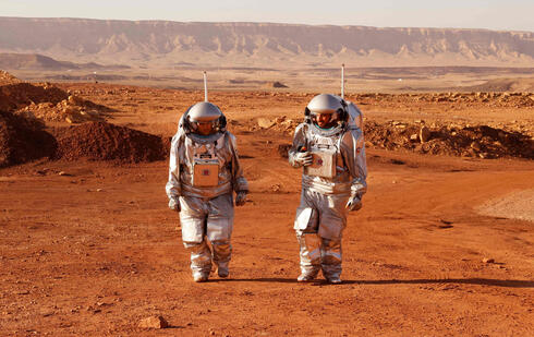 Astronauts from a team from Europe and Israel walk in spacesuits during a training mission for planet Mars at a site that simulates an off-site station at the Ramon Crater in Mitzpe Ramon in the southern Negev desert on October 10, 2021