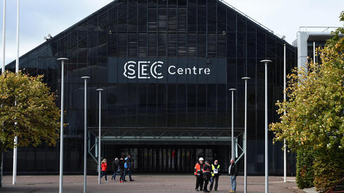 Workers stand outside the SEC Centre in Glasgow on October 4, 2021 as the city prepares to host the COP26 UN Climate Summit in November