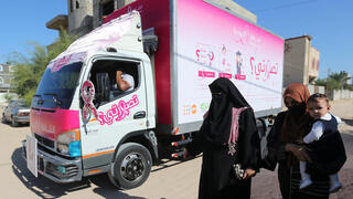 Palestinian women walk past a mobile breast cancer check up clinic set up in a truck, during a campaign aimed to raise public awareness in Gaza