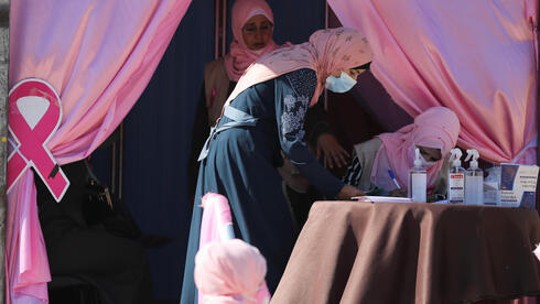 A Palestinian woman registers before a breast cancer check up inside a mobile clinic set up in a truck, during a campaign aimed to raise public awareness in Gaza