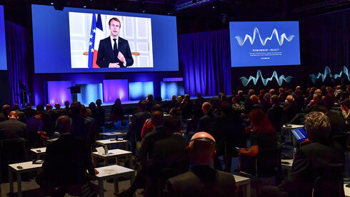 France's President Emmanuel Macron appears on a screen at the Malmo International Forum on Holocaust Remembrance and Combating Antisemitism, in Malmo, Sweden