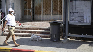 A man walks a dog near a trash can installed next to a bus stop that applauds those who use it, in Jerusalem, October 14, 2021