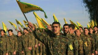 Hezbollah fighters hold flags as they attend the memorial of their slain leader Sheik Abbas al-Mousawi, who was killed by an Israeli airstrike in 1992, in Tefahta village, south Lebanon