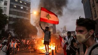 A protester holds a flag during clashes with armed forces in Lebanon, whose economy is in a tailspin