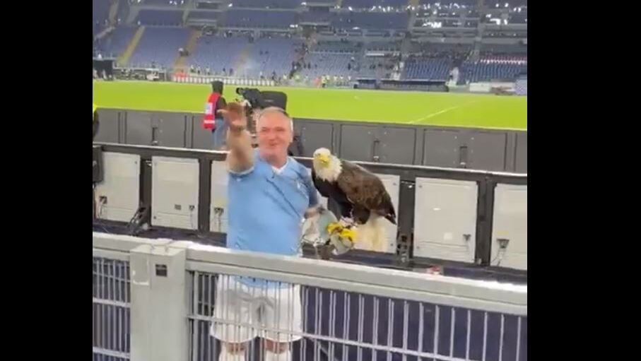 man holding a live eagle - Lazio's mascot- and wearing the blue and white colors of Lazio as he stands in front of the team's supporters at the stadium, raising his arm in the fascist salute