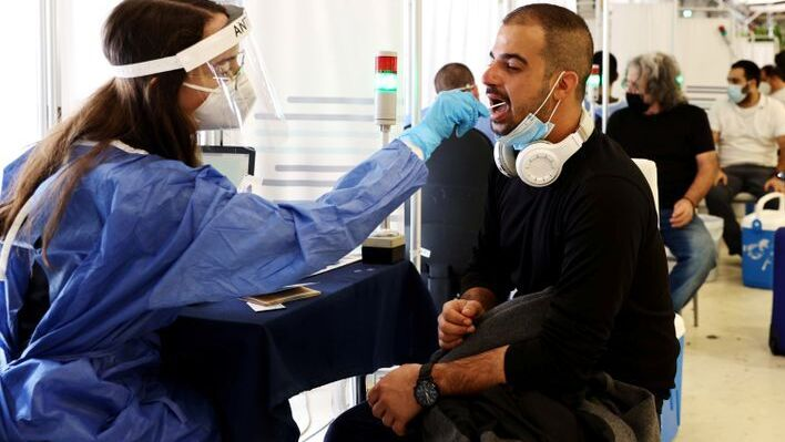 A healthcare worker takes a swab sample from a traveller for a coronavirus disease (COVID-19) test at the Ben Gurion International Airport