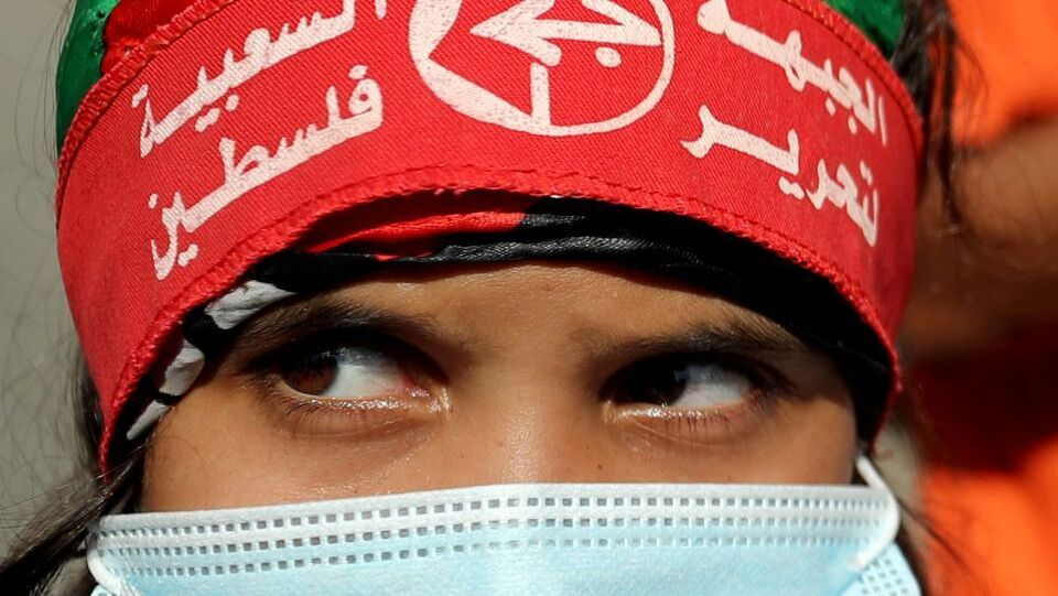 A girl wearing a protective face mask and the headband of the Popular Front for the Liberation of Palestine (PFLP) looks on during a rally to show solidarity with hunger-striking Palestinian prisoner Maher Al-Akhras, who is held by Israel, in Gaza