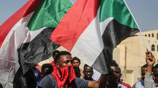 A protester waves a flag during what the information ministry calls a military coup in Khartoum, Sudan