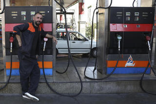 A worker leans against a gasoline pump that has been turned off, at a gas station in Tehran, Iran, Tuesday, Oct. 26, 2021