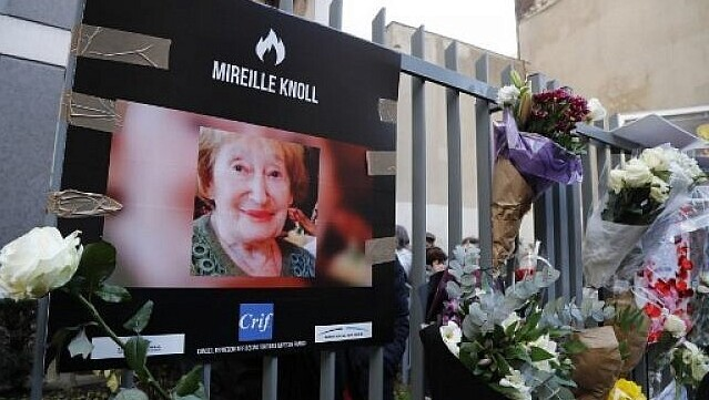 A photograph of murdered Holocaust survivor Mireille Knoll is placed along with flowers on the fence surrounding her building in Paris on March 28, 2018